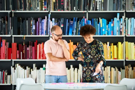 EY - People standing in front of shelves with rainbow colored books